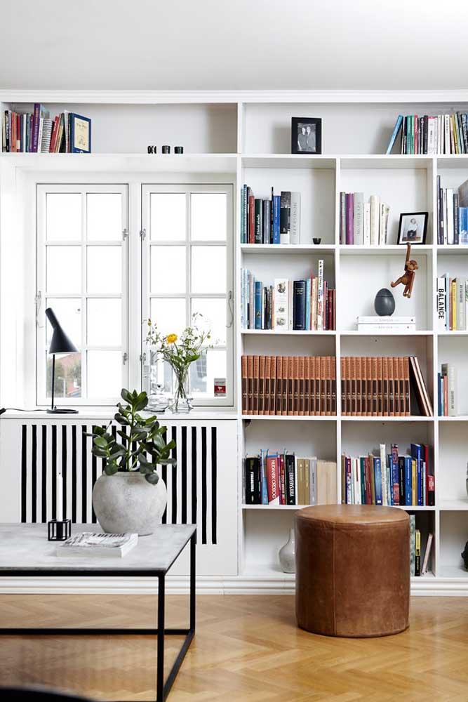Puff redondo alto revestido em couro; o objeto completa a decoração e fica a postos para quando for necessário