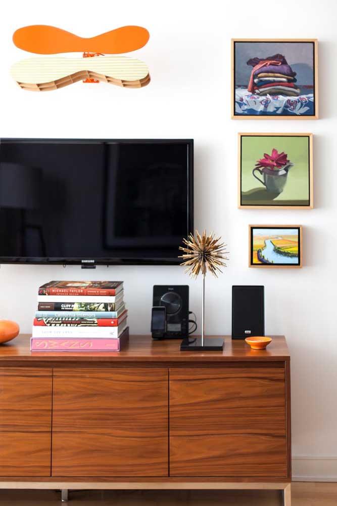 Os quadros pequenos ao lado da TV destacam a parede