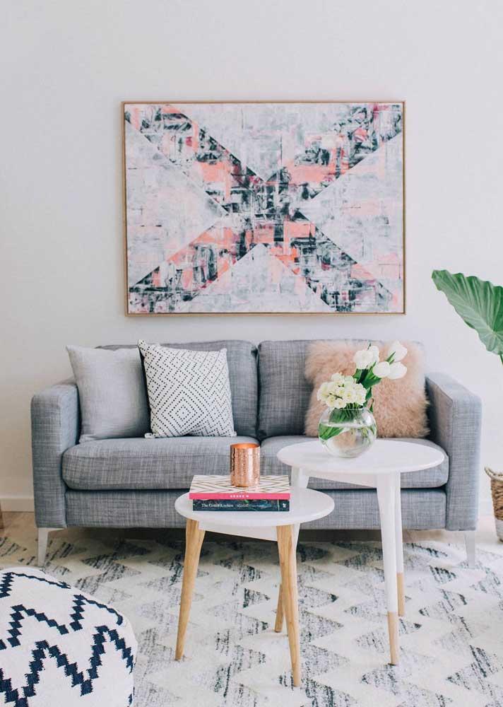 A sala de decoração escandinava traz um quadro grande ocupando toda a área central atrás do sofá; repare que as cores do quadro estão em harmonia com a decor