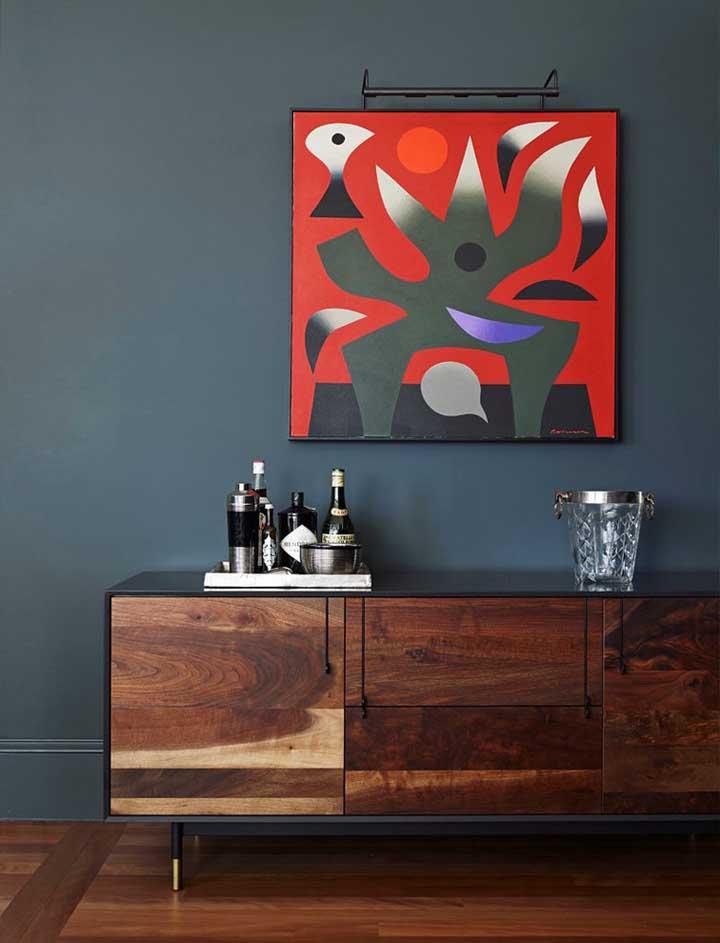 A parede azul petróleo recebeu muito bem o quadro com pintura vermelha