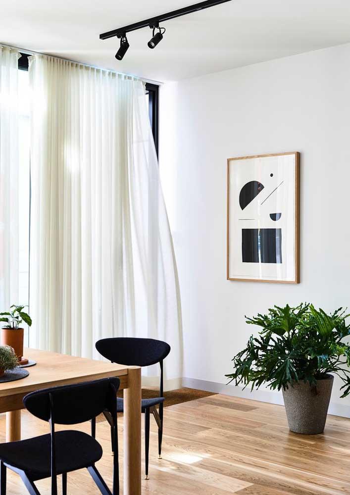O conceito minimalista dessa sala de jantar permitiu que apenas um quadro fosse colocado na parede; mas repare em um efeito interessante, o vaso de planta quebra a percepção do tamanho real da parede e induz a um novo centro focal, justamente onde está o quadro