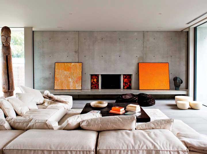 Nessa sala industrial, o laranja dos quadros aquece o ambiente