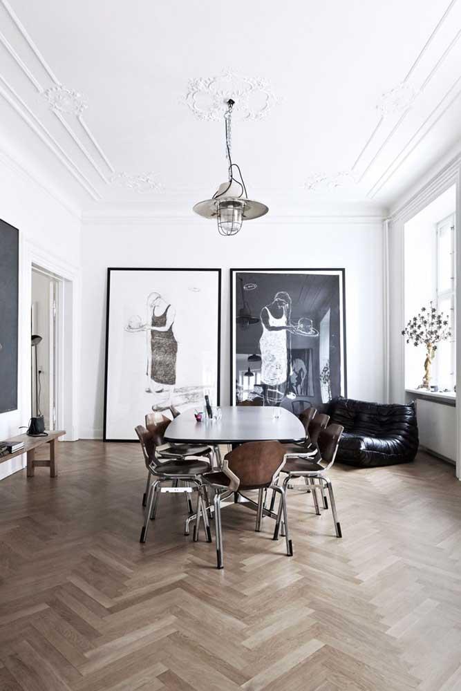 Para esse ambiente minimalista, a escolha foi por dois quadros grandes apenas encostados no chão