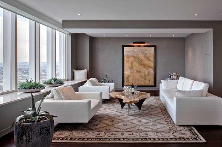 Antigo mapa da Itália decora a parede dessa ampla sala de estar; destaque para a luz direcionada que valoriza ainda mais o quadro