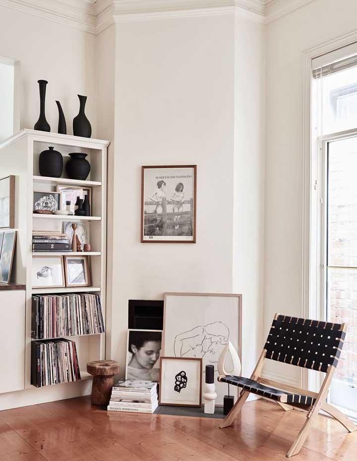 Quadros na parede e no chão, formando uma composição moderna para a sala