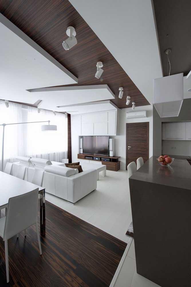 O branco e a madeira escura se combinam com classe e estilo nessa ampla sala planejada; destaque para o teto recortado
