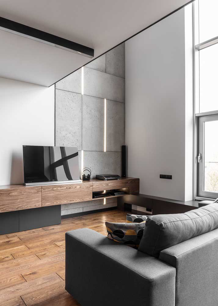 Placas de cimento queimado destacam o pé direito alto dessa sala de estar planejada