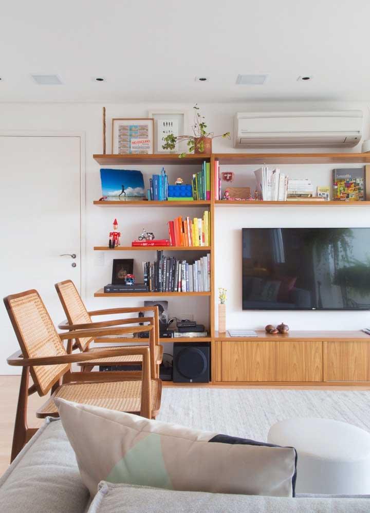 Sala planejada pequena e simples com destaque para a estante de madeira em modelo tradicional