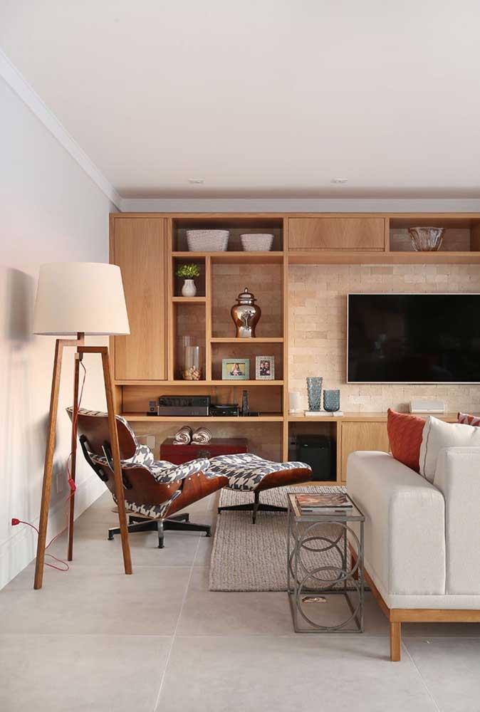 A poltrona com luminária forma um cantinho de leitura aconchegante na sala de estar