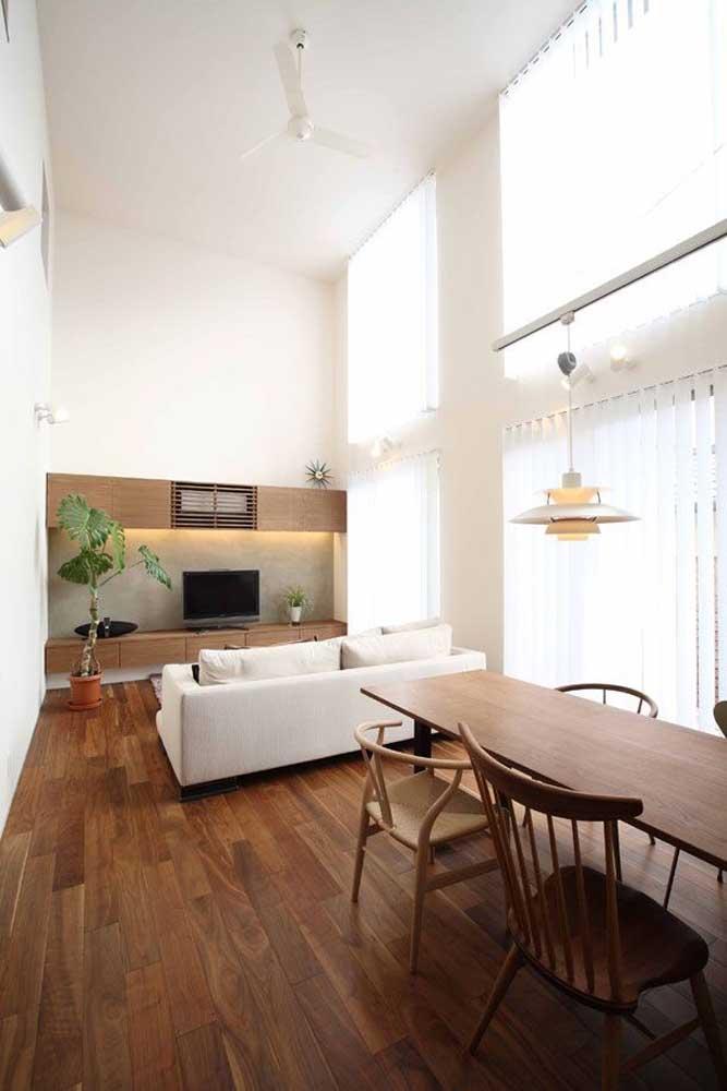 Apesar do pé direito alto, essa sala de estar integrada é pequena; para ajustar as medidas, a solução foi investir no branco
