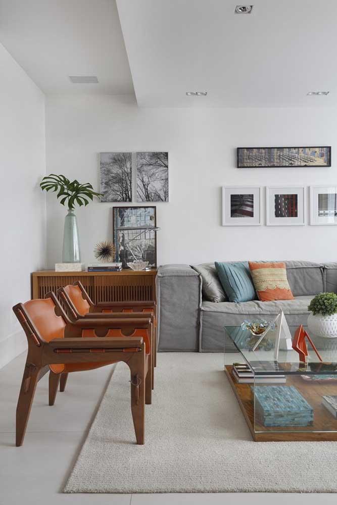 Sala de estar planejada em tons claros e neutros; o destaque fica por conta dos poucos e pontuais móveis de madeira
