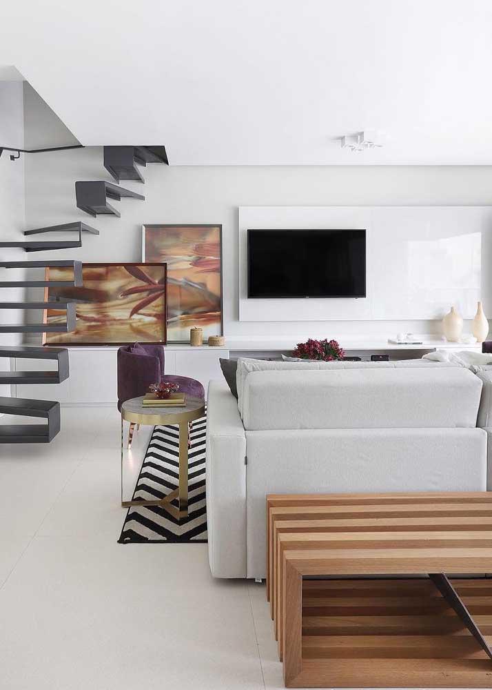 Sala de estar planejada branca com pequenos detalhes em cor para dar vida ao ambiente