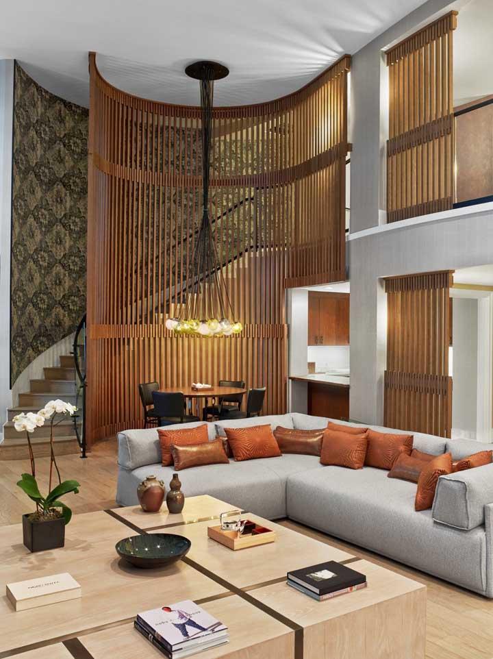 Essa sala planejada grande e espaçosa conta com um belo e original painel de madeira em formato arredondado para destacar o pé direito alto