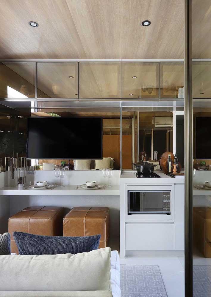 Projeto de sala de estar pequena integrada: a TV fica sobre a parede espelhada, logo abaixo dela, um balcão para refeições com puffs