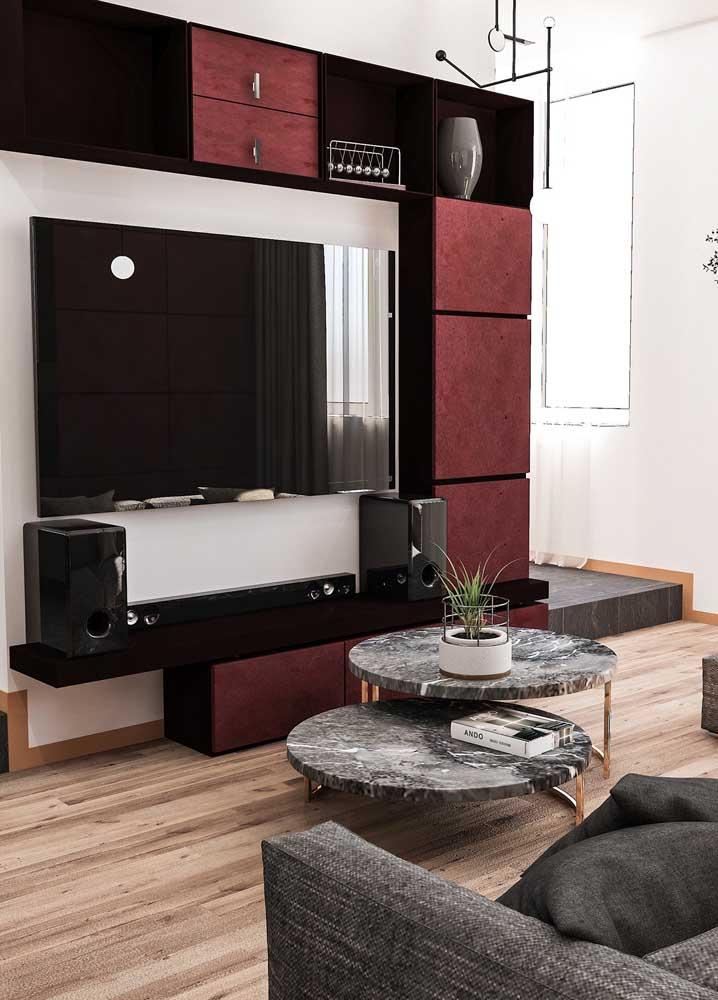 """O tom de vermelho queimado no painel planejado confere elegância e """"quentura"""" a sala de estar"""