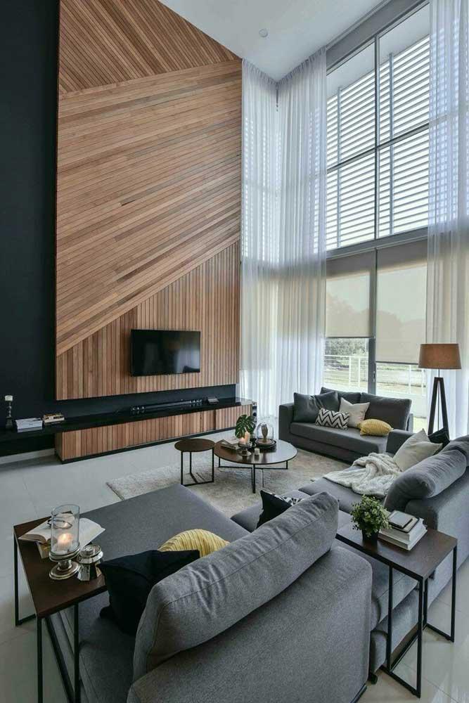 Quem tem a sorte de contar com um pé direito alto na sala de estar precisa saber como valorizá-lo; a sugestão aqui é usar ripas de madeira para formar um painel