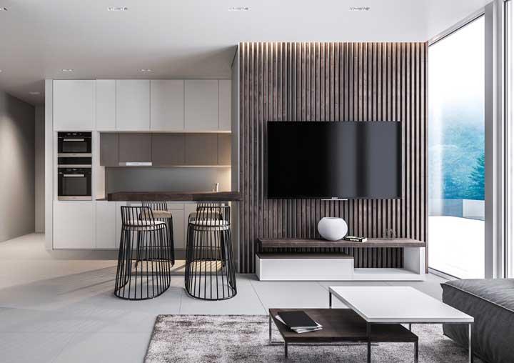 Nessa sala de estar integrada, o painel de madeira para TV termina em um balcão