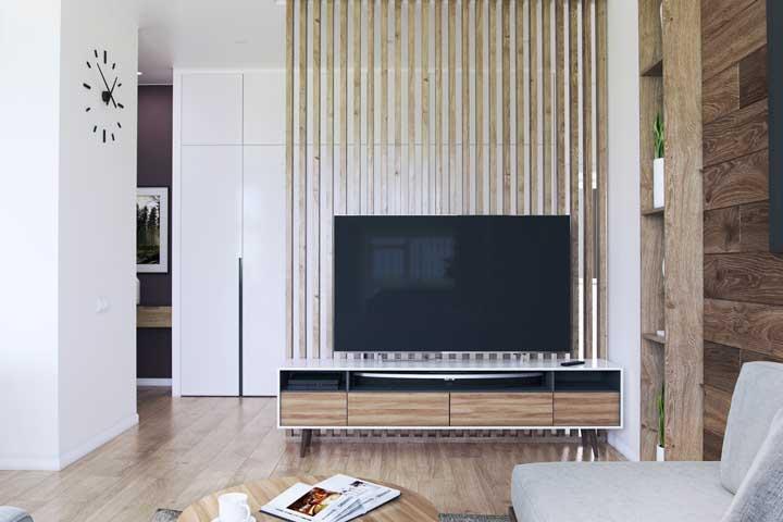 Nessa sala de estar, o painel ripado de madeira possui dupla função: apoio para TV e divisor de ambientes