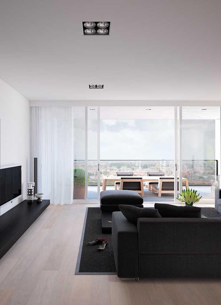 Sala grande planejada em branco e preto; poucos móveis para garantir um ambiente clean e moderno