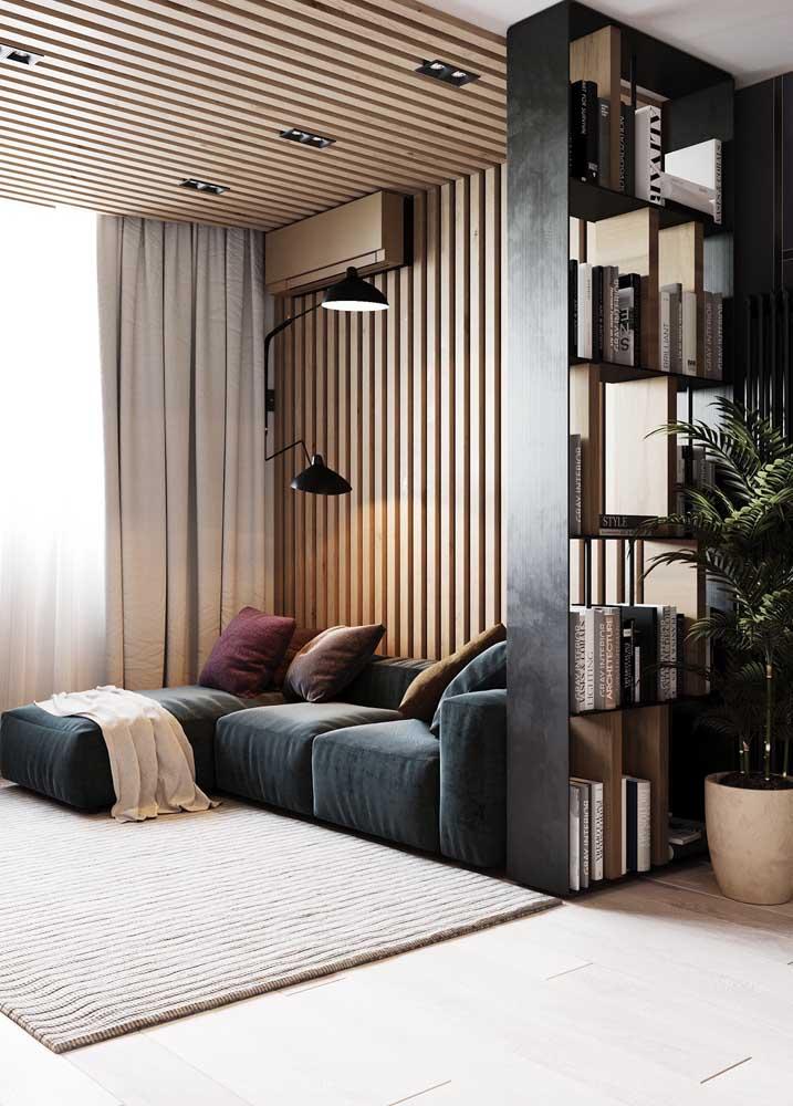 Nessa sala planejada, o destaque fica por conta do revestimento de madeira que começa na parede e se estende até o teto; na lateral, os nichos fazem uma separação sutil entre os ambientes integrados