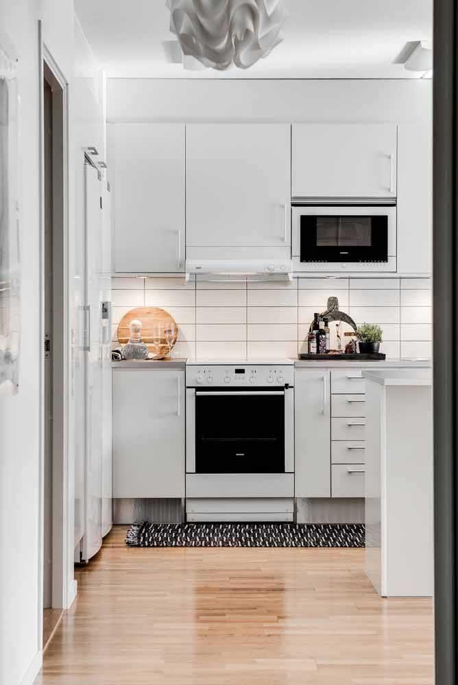 Para deixar a cozinha off white mais moderna, você pode usar um tapete de crochê mesclando as cores preta e branca.