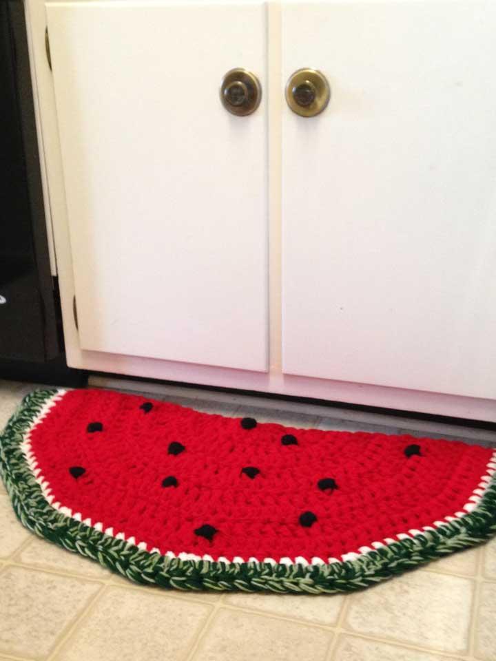 Uma boa ideia é criar um tapete de crochê no formato de fruta como é esse caso da fatia de melancia.