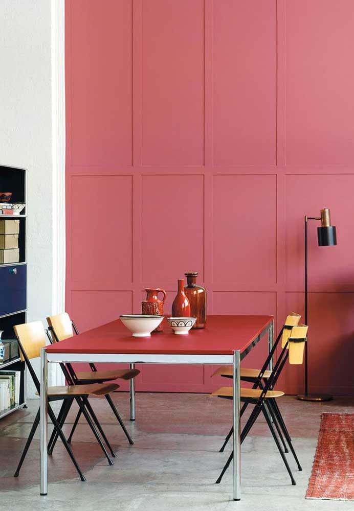 Na sala de jantar, a parede rosa é o grande destaque do ambiente.