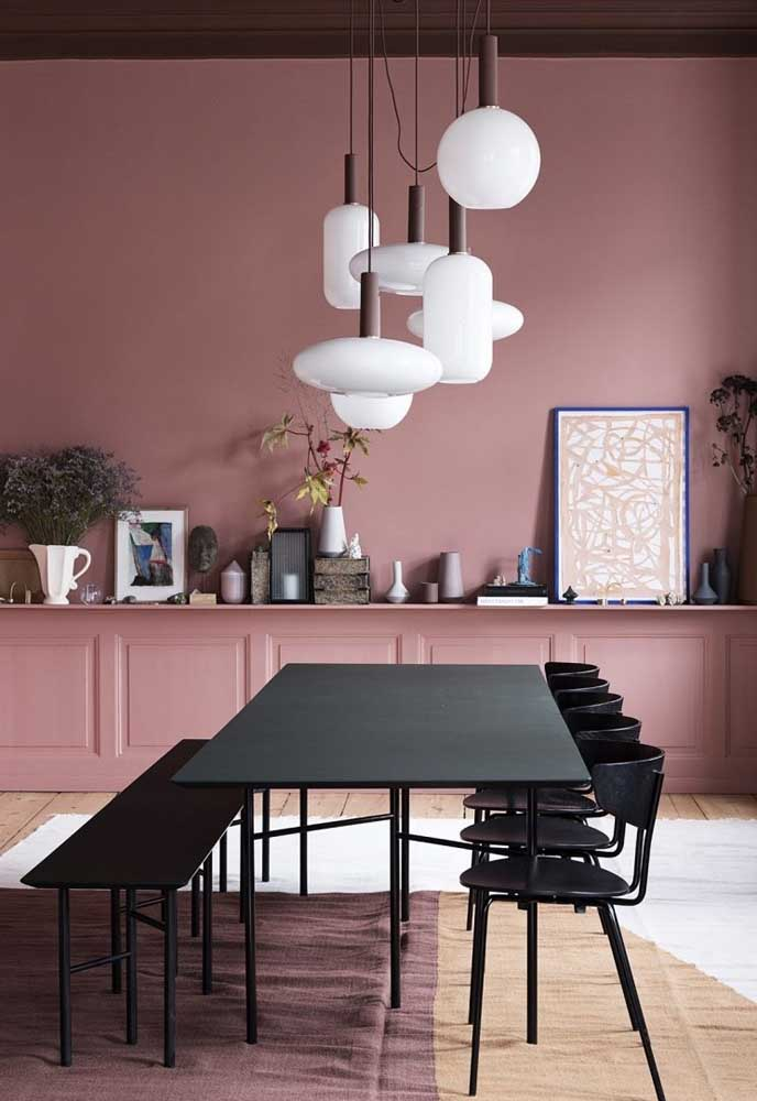 Em uma decoração predominantemente rosa, o conjunto de mesas e cadeiras na cor preta ganha destaque.
