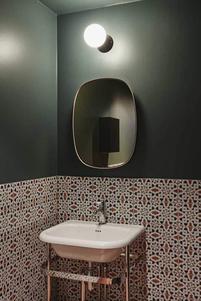 O azulejo de banheiro em alto relevo contrastando com o tom de verde da parede; projeto original e cheio de estilo
