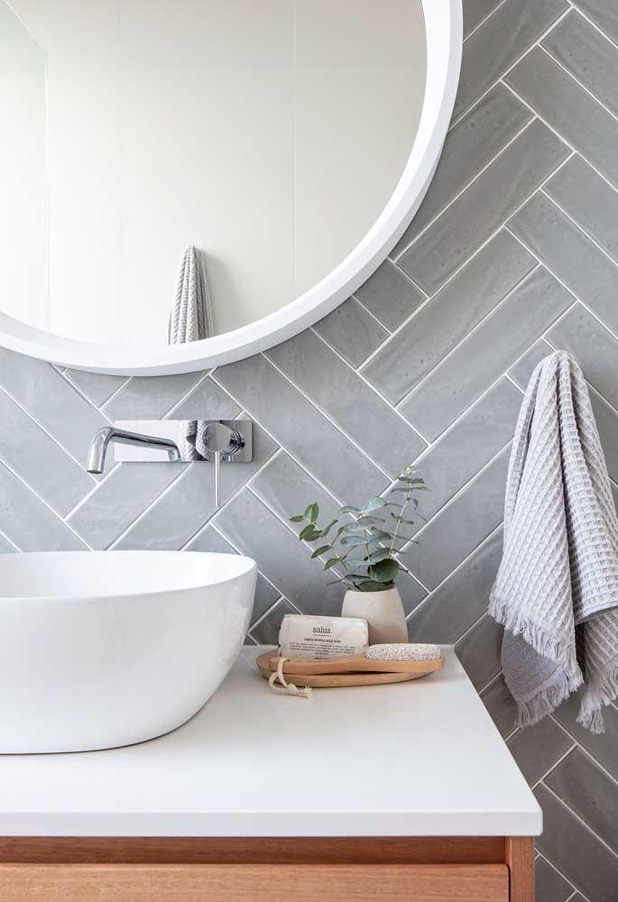 O azulejo cinza desse banheiro garantiu um ar neutro e clássico para o ambiente; destaque para a forma em que foram aplicados