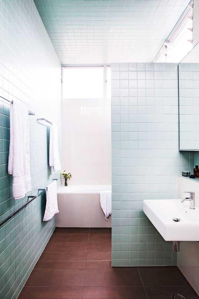 Azulejo de banheiro simples, em tom de azul pastel formando um delicado contraste com o chão avermelhado