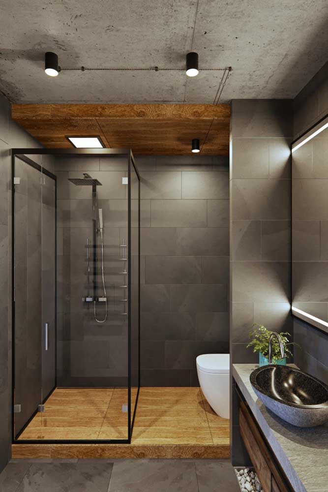 Banheiro moderno com azulejos cinza em placas retangulares; a iluminação contracenou perfeitamente com as peças