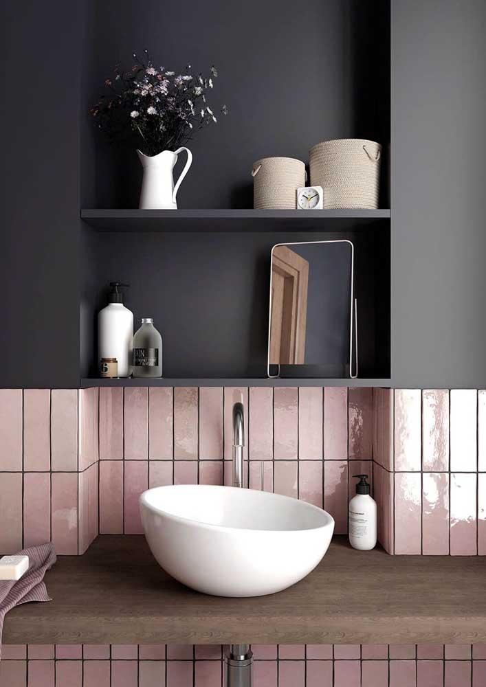Esse banheiro contou com azulejos de metrô rosa formando um contraste incrível com a parede preta na metade superior da parede