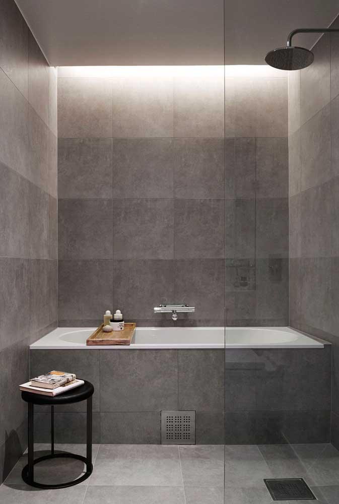 A banheira e as paredes deste banheiro contaram com azulejos que imitam cimento queimado