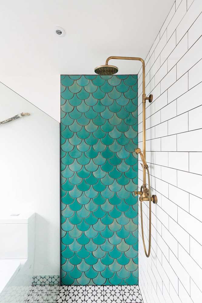 O desenho de escama de peixe dos azulejos deste banheiro são originais e super bonitos; as diferentes tonalidades de azul fecham o projeto