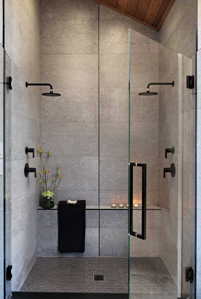 Placas de azulejos cinza foram escolhidas para compor a área do box desse banheiro super moderno