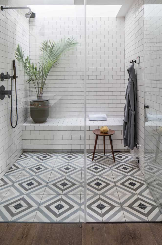Banheiro moderno e clean com azulejos de metrô na cor branca, completando o visual do piso