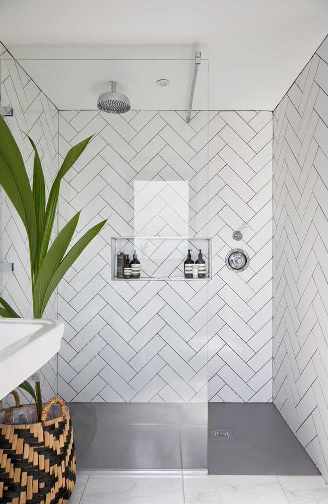 Azulejos de banheiro em retângulos brancos aplicados, inclusive, por dentro do nicho na parede do box