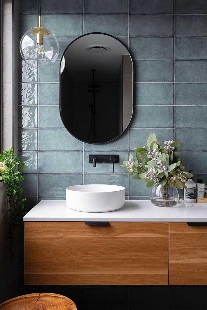 Banheiro com azulejo de acabamento brilhante aplicado na parede de maior destaque, a que fica junto à pia