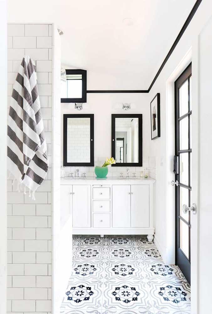Esse banheiro grande ficou incrível com os azulejos brancos contrastando com o piso desenhado; os tons claros ajudam a propagar a iluminação no ambiente