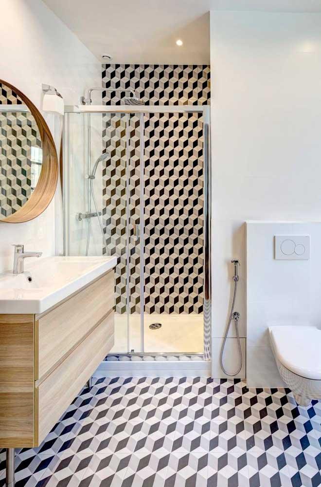 O revestimento em 3D desse banheiro sai do piso e chega até a parede do box