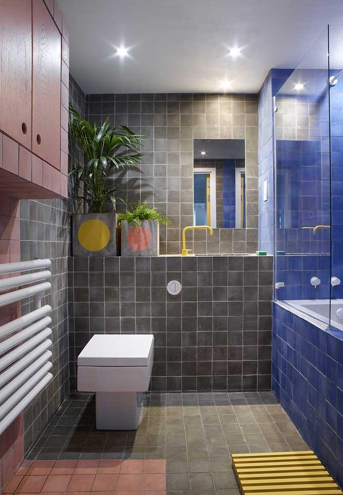Há uma mistura de cores nesse banheiro que estão presentes no revestimento das paredes e nos móveis que fazem parte da decoração.