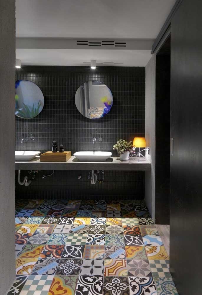 Para quebrar a seriedade do ambiente com a parede escura, invista no piso totalmente colorido.
