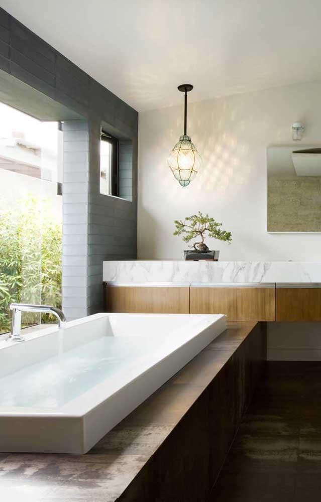 Nesse outro banheiro, o bonsai fica sobre a bancada de frente à banheira