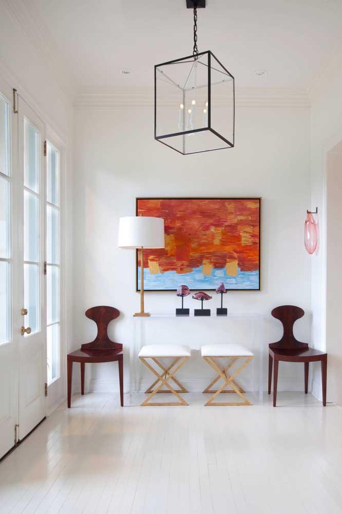 O hall de entrada da casa ganhou a companhia de duas cadeiras de acrílico na cor marrom