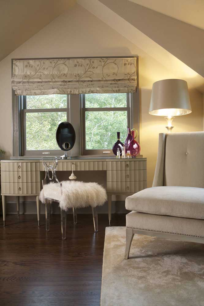 Para o quarto de design clássico a opção foi por uma cadeira de acrílico com almofada de pelúcia