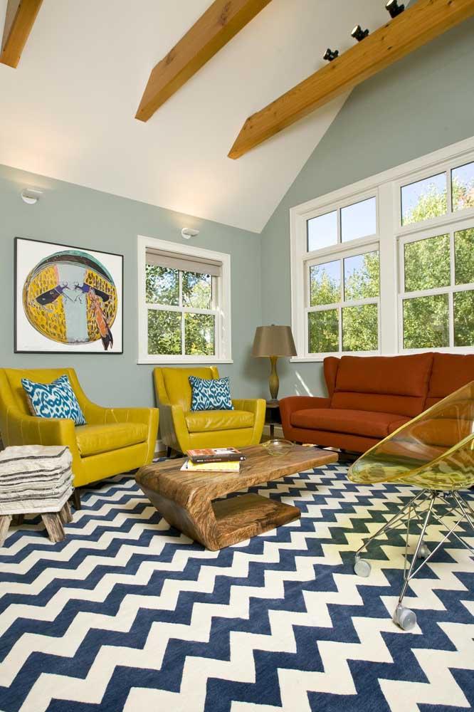 Essa sala de estar contemporânea apostou em um modelo de cadeira de acrílico amarelo; destaque para as rodinhas da peça