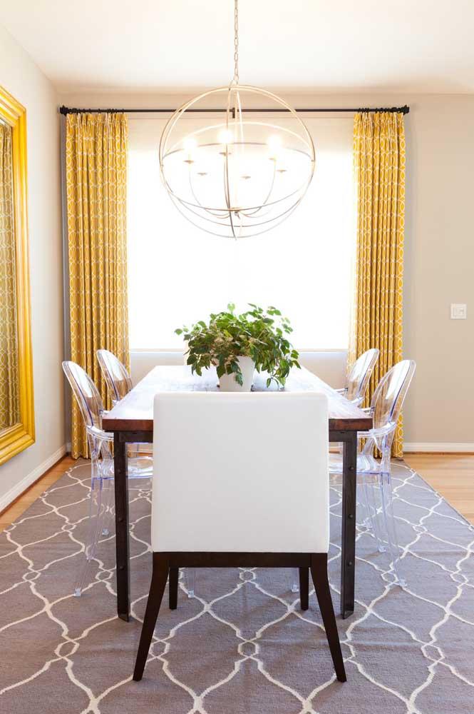 Essa sala de jantar apostou em cadeiras de acrílico transparente usadas em conjunto com as clássicas cadeiras estofadas