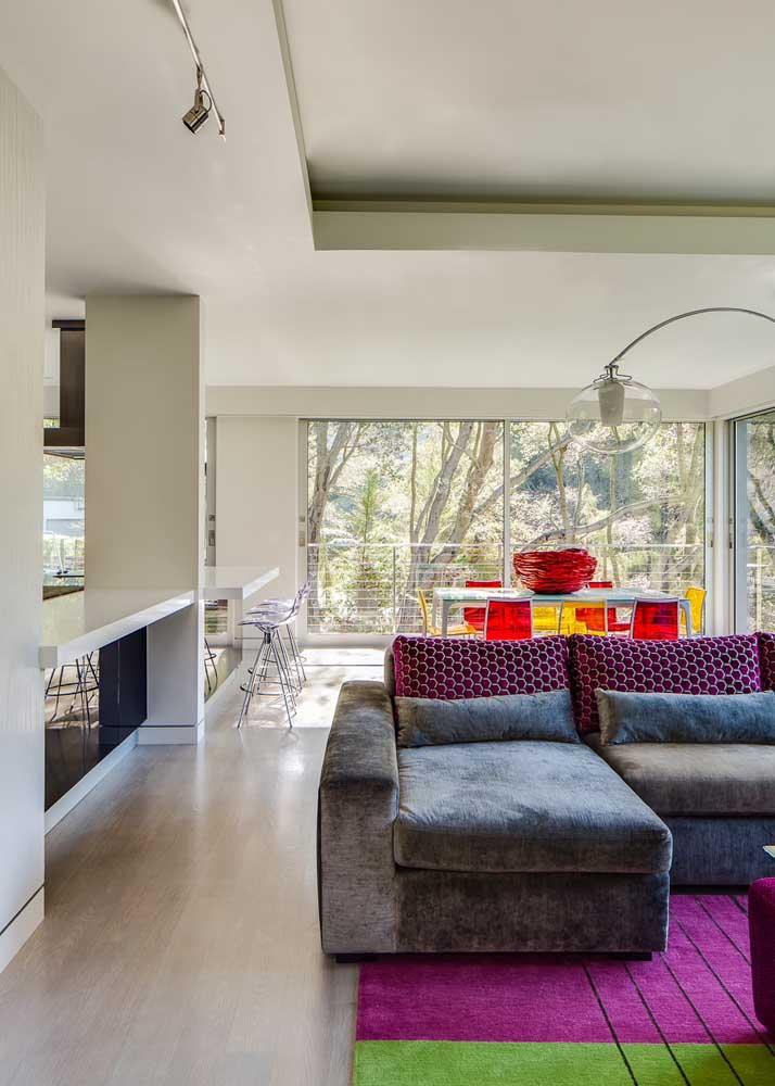 O ambiente integrado ganhou como destaque as cadeiras de acrílico colorido para a mesa de jantar, alternando entre o vermelho e o amarelo