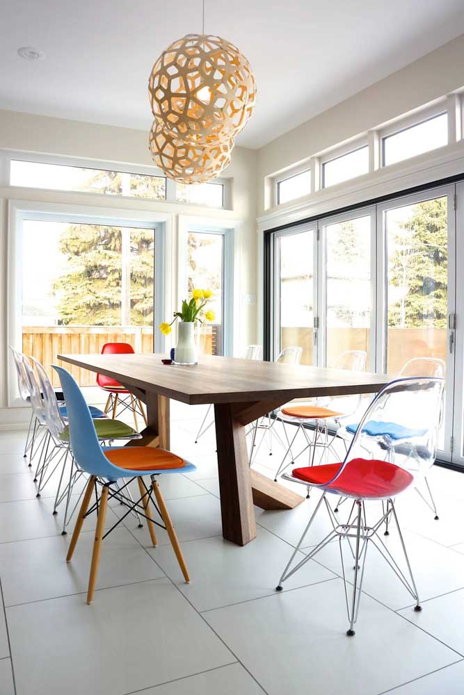 Que sala de jantar linda! As cadeiras de acrílico com almofadas coloridas mudaram totalmente o estilo do ambiente